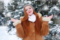 Piękna kobieta na zimie plenerowej, śnieżni jedlinowi drzewa w lesie, długi czerwony włosy, jest ubranym barankowego żakiet Obrazy Stock