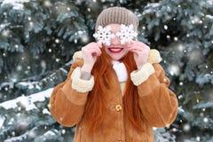 Piękna kobieta na zimy plenerowy pozować z dużym płatkiem śniegu bawi się, wakacyjny pojęcie, śnieżni jedlinowi drzewa w lesie, d Obraz Stock