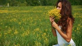 Piękna kobieta oddycha żółtych kwiaty w zielenieje pole zbiory wideo