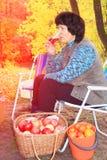 Piękna kobieta odpoczywa w ogródzie na słońca lounger no pije soku po podnosić jabłka fotografia royalty free