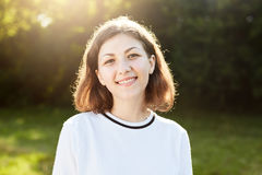 Piękna kobieta ono uśmiecha się przyjemnie w kamerę z krótkim włosy i interesującym pojawieniem podczas gdy odpoczywający outdoor obrazy stock