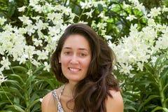 Piękna kobieta ono uśmiecha się w bez makeup orchidee uprawia ogródek zdjęcia royalty free