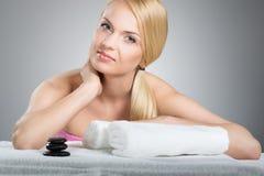 Piękna kobieta opiera na stole z ręcznikami i zdrojów kamieniami Obrazy Royalty Free