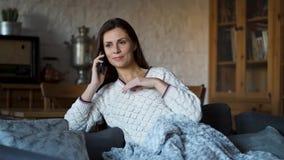 Piękna kobieta opowiada na telefonie na leżance zawijającej w koc zbiory wideo