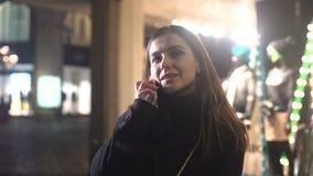 Piękna kobieta opowiada smartphone, czekać na przyjaciela na nocy miasta ulicie zbiory wideo