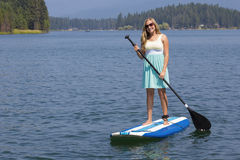 Piękna kobieta paddleboarding na scenicznym jeziorze Fotografia Royalty Free
