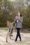 Piękna kobieta patrzeje kamerę na bicyklu w parku Obrazy Stock