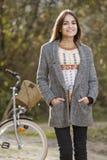 Piękna kobieta patrzeje kamerę na bicyklu w parku Obraz Stock