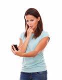 Piękna kobieta patrzeje na jej telefonie komórkowym Zdjęcie Royalty Free