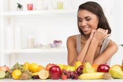Piękna kobieta patrzeje owoc na stole Fotografia Stock