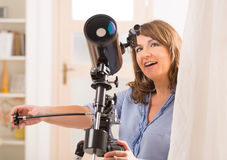 Piękna kobieta patrzeje przez teleskopu obraz royalty free