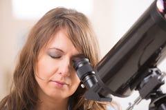 Piękna kobieta patrzeje przez teleskopu fotografia royalty free