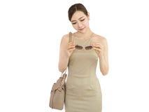 Piękna kobieta patrzeje szkła, mody dziewczyny mienia torebka Obrazy Royalty Free