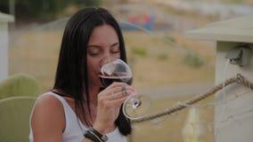 Piękna kobieta pije czerwone wino na tarasie w restauracji zbiory