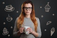 Piękna kobieta pije herbaty i główkowania o łasowanie cukierkach zdjęcie stock