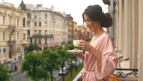 Piękna kobieta pije kawę na balkonie stary dom zbiory wideo