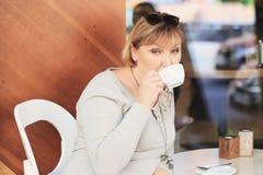 Piękna kobieta pije kawę w kawiarni Zdjęcie Royalty Free