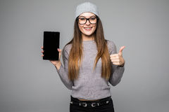 Piękna kobieta pokazuje mądrze telefon z kciukiem up odizolowywającym na popielatym tle Fotografia Royalty Free