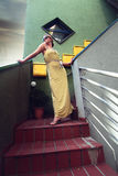 Piękna kobieta pozuje w długiej kolor żółty sukni na tarasie Zdjęcie Stock
