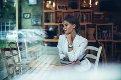Piękna kobieta przy kawiarnią z laptopem obrazy stock