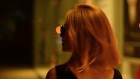 Piękna kobieta przystosowywa włosianych spojrzenia przy kamerą i iść miasto przy nocą zbiory