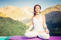 Piękna kobieta relaksuje i medytuje plenerowy przy górą Zdjęcie Royalty Free