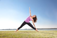 Piękna kobieta robi joga ćwiczeniu na zielonej trawie Zdjęcia Stock