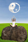 Piękna kobieta robi joga medytaci pod ying Yang chmurę Obraz Royalty Free