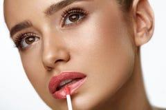 Piękna kobieta Robi Makeup Używać wargi glosę Na wargach Kosmetyki Fotografia Royalty Free