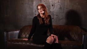 Piękna kobieta siedzi na brown leżance i trzyma rękę na jej nagim kolanie zbiory wideo