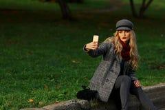 Piękna kobieta siedzi na drodze i brać selfie z smartphone w jesień parku Zdjęcie Royalty Free