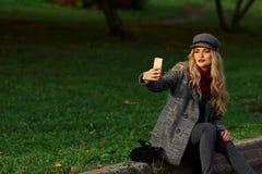 Piękna kobieta siedzi na drodze i brać selfie z smartphone w jesień parku Obrazy Stock