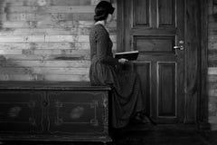 Piękna kobieta siedzi w profilu na czarnej klatce piersiowej i czyta książkę na drewnianym tle obraz royalty free