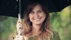 Piękna kobieta stoi pod parasolem podczas deszczu cieszy się naturę szczerze śmiać się i, zbiory
