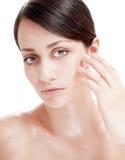 Piękna kobieta stosuje kosmetycznego kremowego traktowanie na jej twarzy. zdjęcie stock