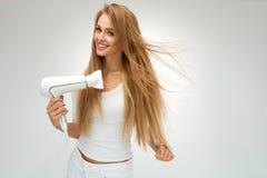 Piękna kobieta Suszy Prostego włosy Używać suszarkę hairdryer zdjęcie stock