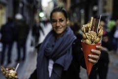 Piękna kobieta trzyma bąbla gofra z lody i cukierki na czerwień papierze konusujemy z zamazanym unrecognizable tłumem na zdjęcia stock