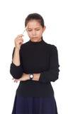 Piękna kobieta trzyma białego pióro był ubranym czarną bluzkę z błękitną spódnicą poważnego główkowanie i coś Fotografia Royalty Free