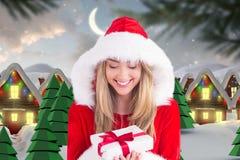 Piękna kobieta trzyma boże narodzenie prezent w Santa kostiumu Fotografia Royalty Free