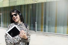 Piękna kobieta trzyma cyfrową pastylkę podczas gdy stojący w s obrazy royalty free