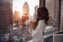 Piękna kobieta trzyma filiżankę i patrzeje okno w luksusowych Manhattan apartament na najwyższym piętrze mieszkaniach Zdjęcia Royalty Free