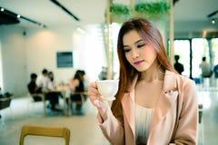 Piękna kobieta trzyma filiżankę kawy w jej ręce w plamy tła sklep z kawą, rocznika styl Zdjęcie Royalty Free