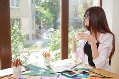Piękna kobieta trzyma filiżanka kawy, patrzeje okno fotografia stock