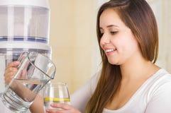 Piękna kobieta trzyma szkło woda w jeden ręce i miotaczu woda w jej innej ręce z filtrowym systemem, Zdjęcia Royalty Free