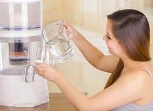 Piękna kobieta trzyma szkło woda w jeden ręce i miotaczu woda w jej innej ręce z filtrowym systemem, Obraz Stock