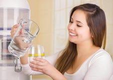 Piękna kobieta trzyma szkło woda w jeden ręce i miotaczu woda w jej innej ręce z filtrowym systemem, Fotografia Stock