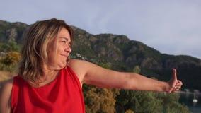 Piękna kobieta uśmiechająca się i ukazująca się za pomocą ręcznego gestu, ok w górach zbiory wideo