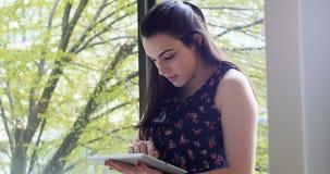 Piękna kobieta używa cyfrową pastylkę blisko okno 4k zbiory wideo