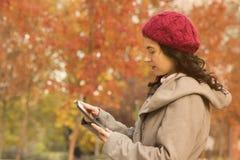 Piękna kobieta używa cyfrową pastylkę outdoors Obraz Royalty Free