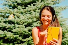 Piękna kobieta używa pastylkę outdoors Fotografia Stock